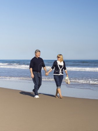 Sportive mature couple walking along the beach