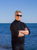 Jistý podnikatel v černé pózuje na pláži