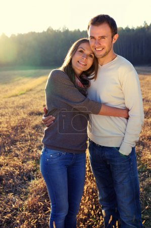 Photo for Young hugging couple in fall with fores in the background - Royalty Free Image