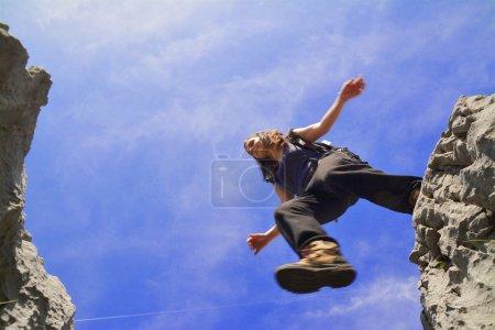 Photo pour Jeune femme sautant au-dessus d'une falaise - image libre de droit