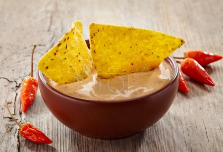 Photo for Bowl of dip and nachos on wooden background - Royalty Free Image