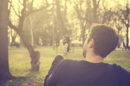 Photo for Young man sitting in the park and texting a message - Royalty Free Image
