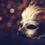 Golden venetian mask over black background...