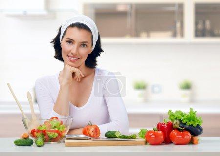 Photo pour Femme dans la cuisine en salade - image libre de droit