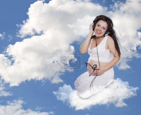 Photo pour Musique pour deux. La femme enceinte dans les écouteurs écoute de la musique - image libre de droit