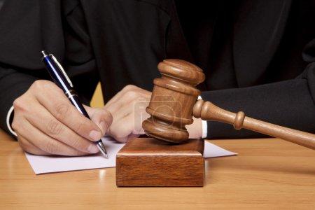 Photo pour Marteau de l'arbitre et un homme en robe judiciaire - image libre de droit