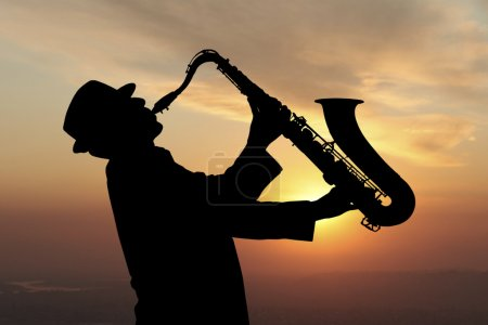 Saxophonist. Man playing on saxophone against the ...