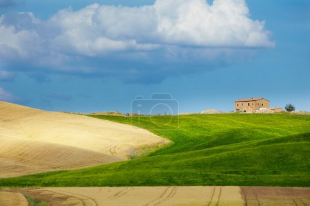 Tuscany landscape with typical farm house on a hill in Val d'Orc