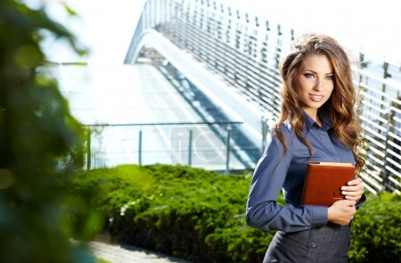Businesswoman standing outside a modern house