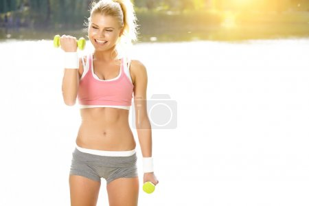 Fitness instructor exercising with small weights in city park