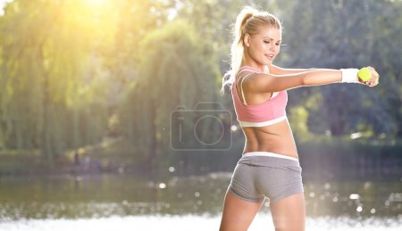 female fitness instructor exercising with small weights