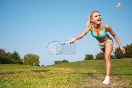 Photo pour Fitness, jeune femme jouant au badminton dans un parc municipal - image libre de droit
