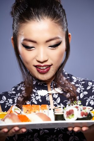 Sushi woman holding sushi with chopsticks looking at the camera