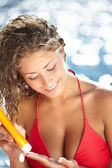 Woman applying sun block solar cream for UV protection