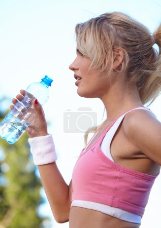Woman drinking water after doing sports