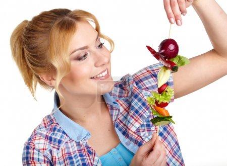 Woman holding vegetable skewers