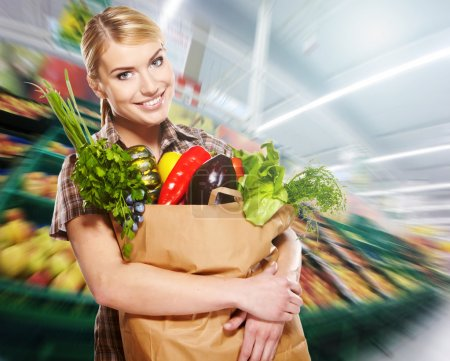 Photo for Young woman with a grocery shopping bag. Shop background. - Royalty Free Image