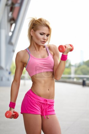 Photo for Female fitness instructor exercising with small weights in city - Royalty Free Image
