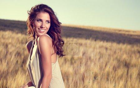 Photo pour Belle jeune femme sur le champ de céréales dorées en été - image libre de droit