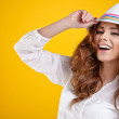 Sexy spring brunette girl with hat in a yellow bac...