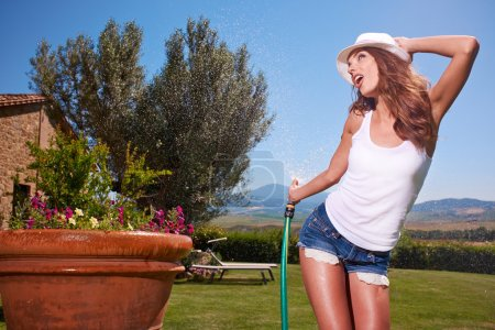 Sexy woman watering flowers