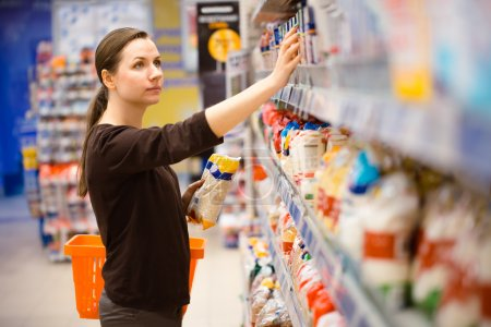 Photo for Beautiful young woman shopping for cereal, bulk in a grocery supermarket - Royalty Free Image