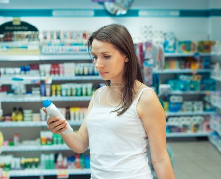 Young woman shopping in the store household chemicals and cosmet