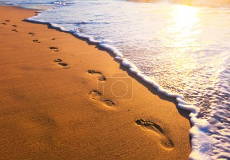 Photo for Beach, wave and footsteps at sunset time - Royalty Free Image