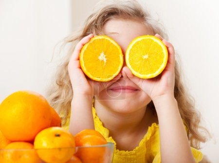 Photo for Child with oranges. Happy little girl with fruit at home. - Royalty Free Image