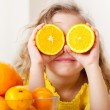 Child with oranges. Happy little girl with fruit a...