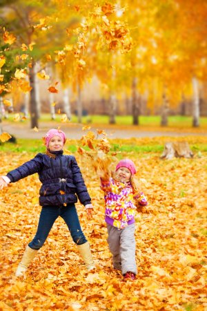Photo for Happy children in autumn park. Kids juggle leaves - Royalty Free Image