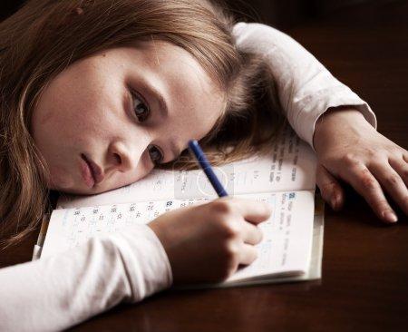 Photo pour Un enfant qui fait ses devoirs. Triste fille écriture, élevage - image libre de droit