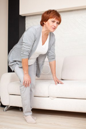 Photo for Adult woman has pain in the knee. Mature female at home - Royalty Free Image