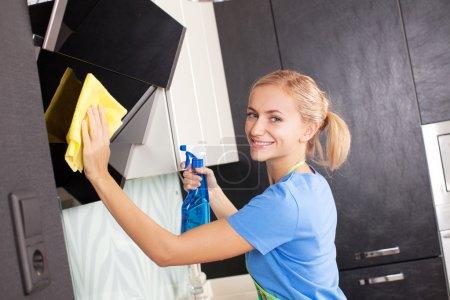 Photo pour Femme de ménage cuisine. Jeune femme lavage hotte de cuisine - image libre de droit
