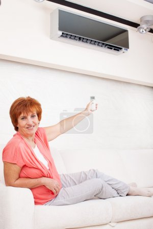 Photo for Woman holding a remote control air conditioner at home. Happy mature woman on sofa - Royalty Free Image