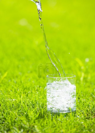 Photo for Water poured into glass. Pure water on green bacground - Royalty Free Image
