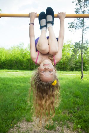 Photo for Child hanging on horizontal bar - Royalty Free Image