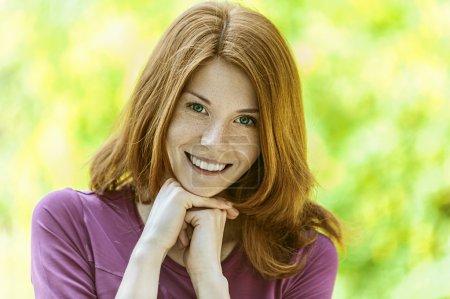 Photo pour Portrait de belle jeune femme aux cheveux roux souriant, contre le vert du parc d'été . - image libre de droit