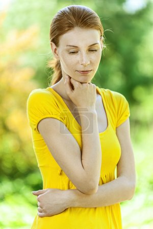 Photo for Portrait of red-haired pensive beautiful young woman in yellow blouse, against green of summer park. - Royalty Free Image