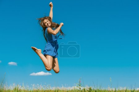 Photo for Beautiful dark-haired happy young woman jumping high in air, against background of summer blue sky. - Royalty Free Image