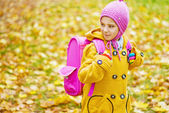 Little girl with pink backpack goes to school