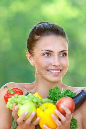Photo pour Portrait d'heureuse belle jeune femme avec des légumes, sur fond de parc d'été vert - image libre de droit