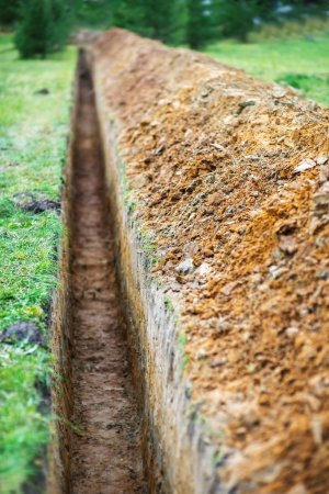 Photo pour Longtemps en terre tranchée creusée pour poser les tuyaux - image libre de droit