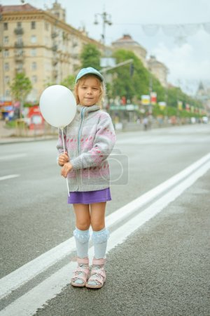 Beautiful little girl with white balloon