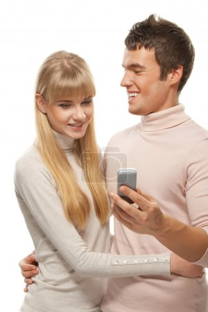 young couple looking at mobile telephone