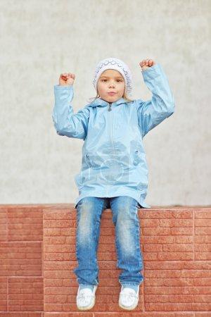 Photo pour Belle petite fille en chapeau blanc et veste autour du bâtiment de l'école . - image libre de droit