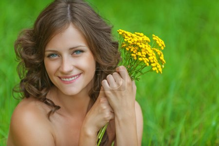 Portrait young beautiful woman holding bouquet yellow wildflower