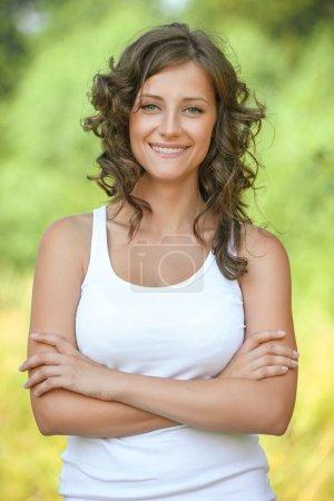Photo pour Portrait beaux cheveux bouclés jeune femme bras croisés souriant parc d'été vert de fond - image libre de droit