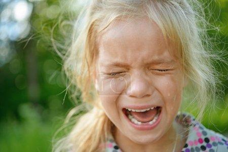 Beautiful sad little girl crying, on summer backgr...
