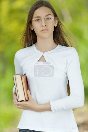Beautiful teenage girl dressed in white with books...